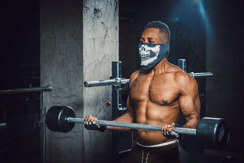Hombre afroamericano joven muscular en barbell de elevación de la máscara en bíceps Ejercicio para el bíceps con el barbell hombr fotos de archivo