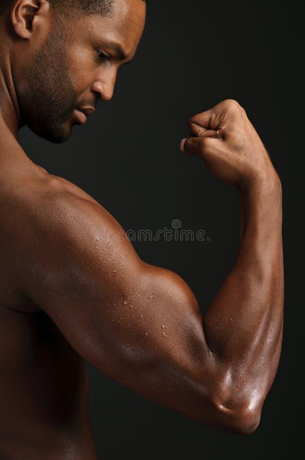 Hombre afroamericano joven que dobla el bíceps imagen de archivo