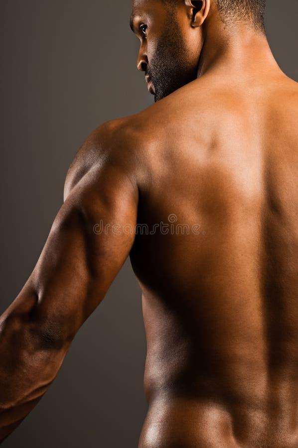 Hombre afroamericano joven que dobla el tríceps fotografía de archivo