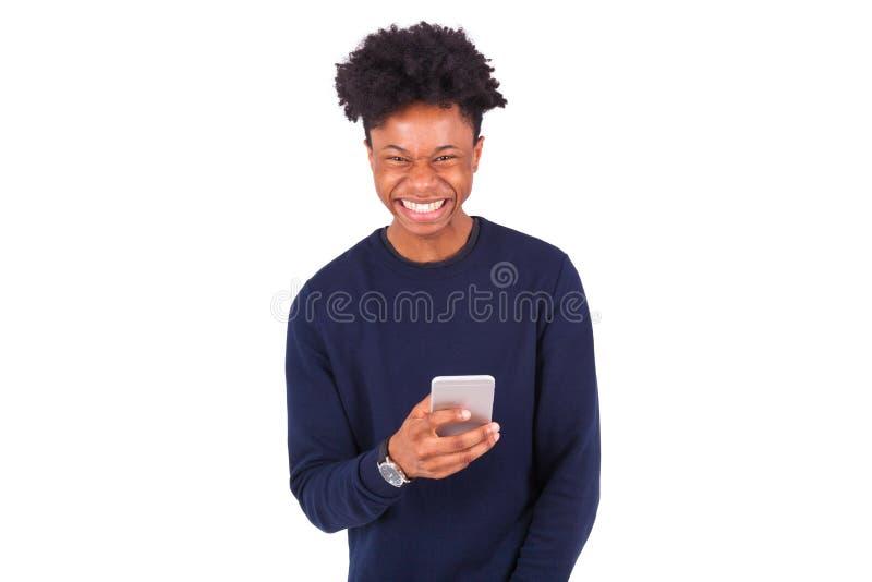 Hombre afroamericano joven que envía un mensaje de texto del SMS en su sma fotos de archivo libres de regalías