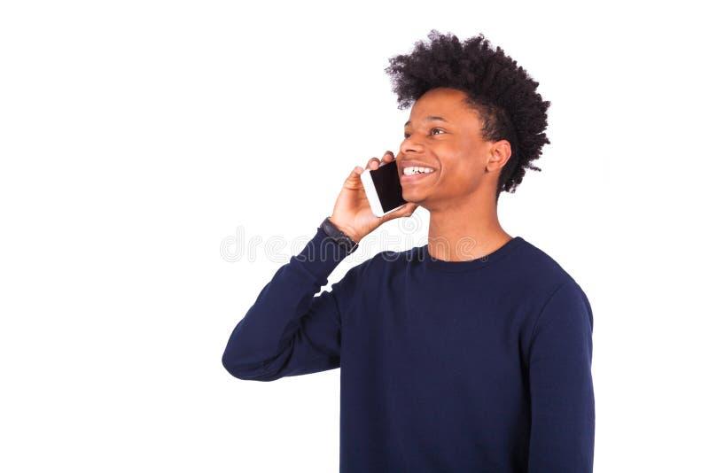 Hombre afroamericano joven que hace una llamada de teléfono en su smartphone imagenes de archivo