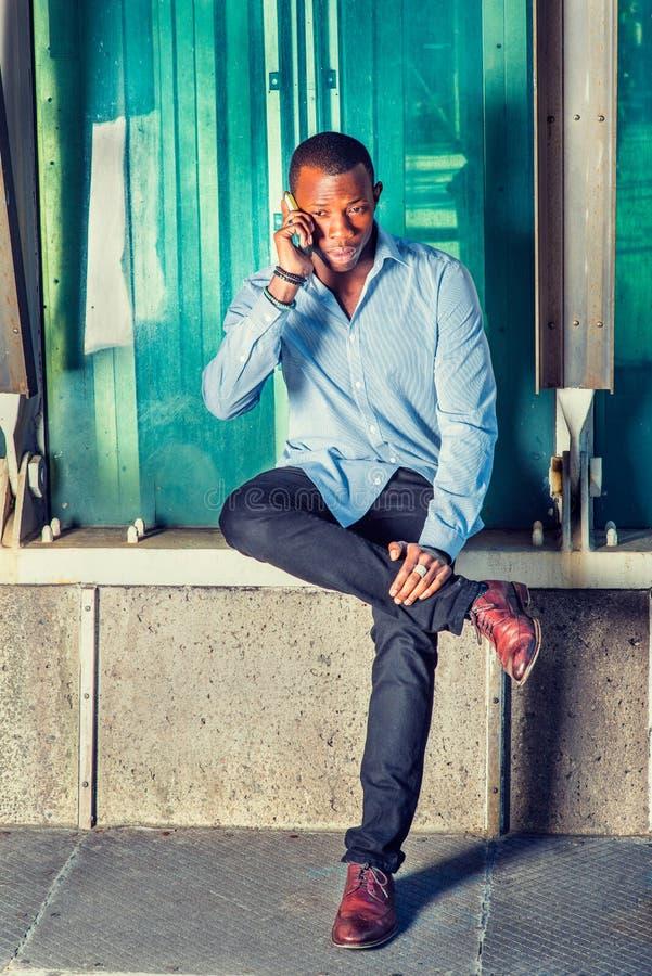 Hombre afroamericano joven que invita al teléfono celular afuera en nuevo fotos de archivo libres de regalías
