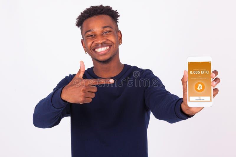 Hombre afroamericano joven que señala su showi de la pantalla del smartphone fotografía de archivo