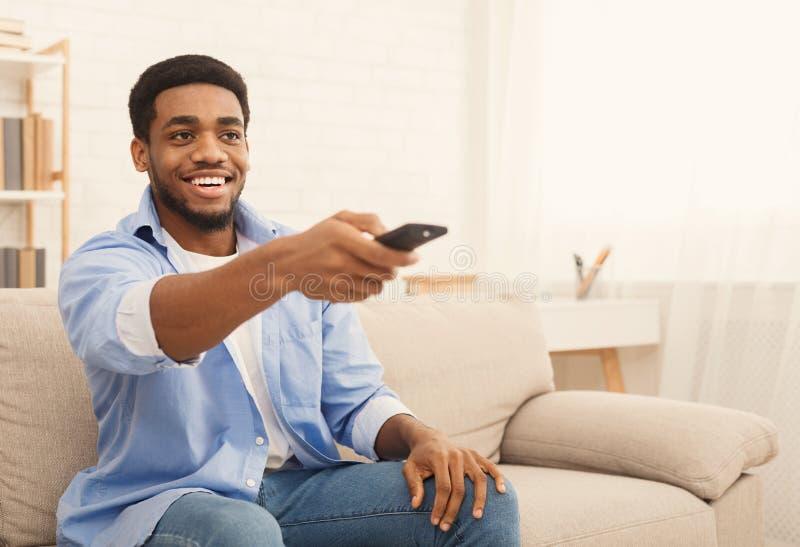 Hombre afroamericano joven que ve la TV en casa fotografía de archivo libre de regalías