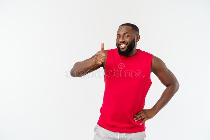 Hombre afroamericano joven sobre desgaste del deporte del fondo que lleva que sonríe con la cara feliz que mira con el pulgar par fotos de archivo