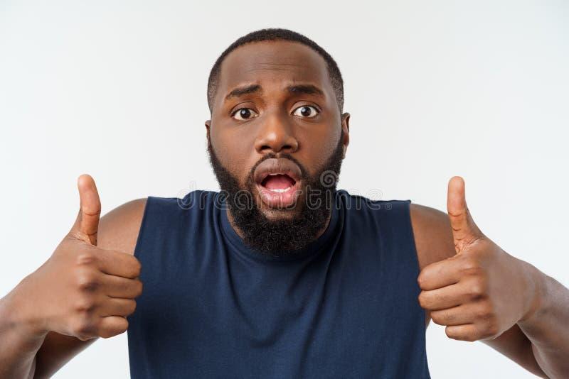 Hombre afroamericano joven sobre desgaste del deporte del fondo que lleva que sonríe con la cara feliz que mira con el pulgar par imagen de archivo libre de regalías
