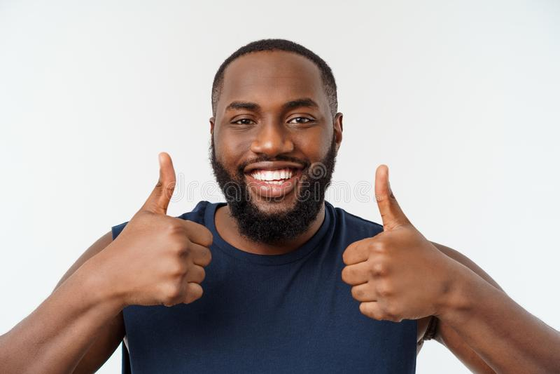 Hombre afroamericano joven sobre desgaste del deporte del fondo que lleva que sonríe con la cara feliz que mira con el pulgar par fotos de archivo libres de regalías