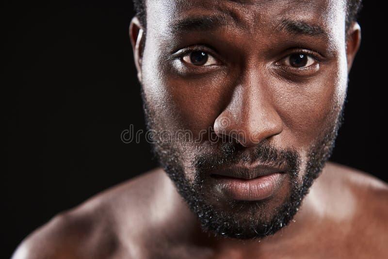 Hombre afroamericano joven trastornado que le mira imagen de archivo libre de regalías