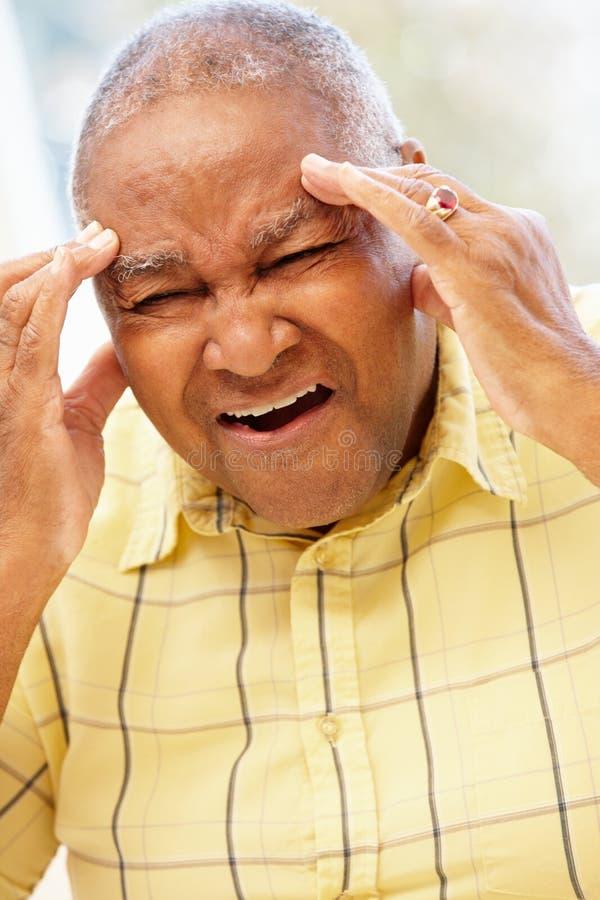 Hombre afroamericano mayor con dolor de cabeza imagen de archivo