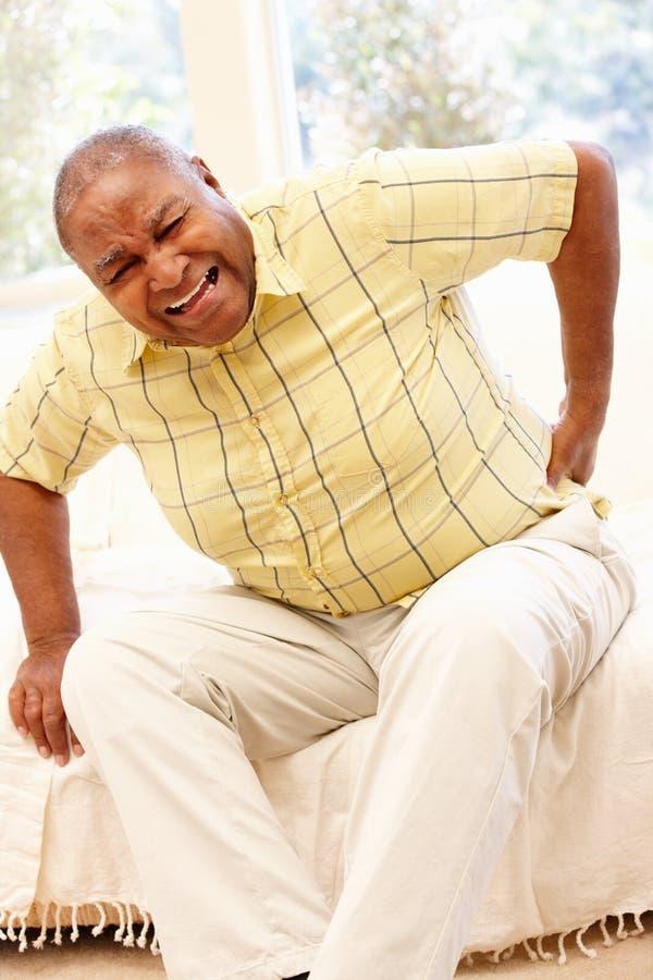 Hombre afroamericano mayor con dolor de espalda fotos de archivo
