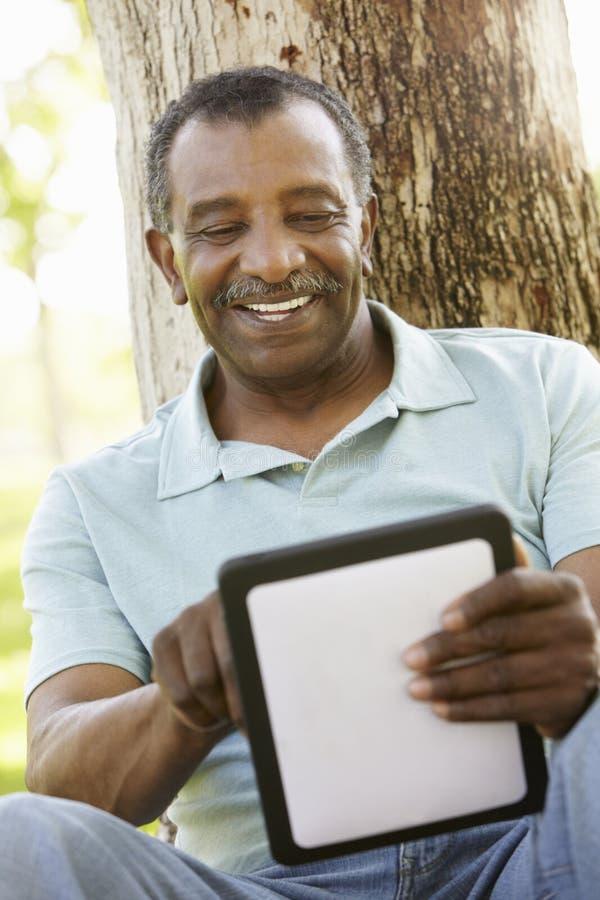 Hombre afroamericano mayor en parque usando la tableta imágenes de archivo libres de regalías