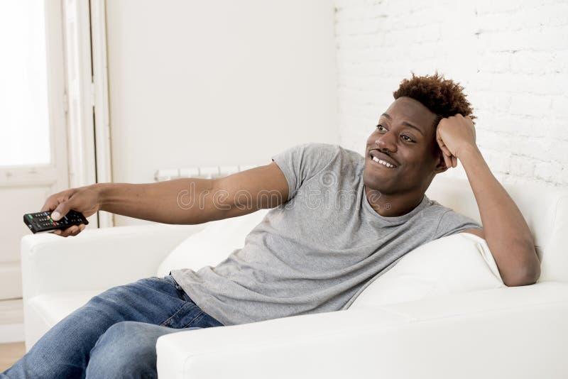 Hombre afroamericano negro atractivo que sienta en casa la televisión de observación del sofá del sofá imagen de archivo libre de regalías