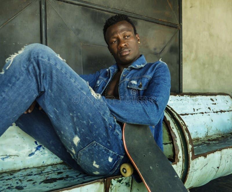 Hombre afroamericano negro atractivo y apto joven que se sienta en el tablero de la esquina del patín de la tenencia del banco de fotografía de archivo libre de regalías