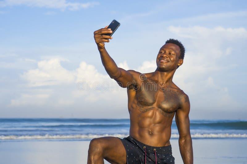Hombre afroamericano negro atractivo y feliz joven del deporte con el cuerpo atlético y sixpack que toma la foto del selfie con e imagenes de archivo