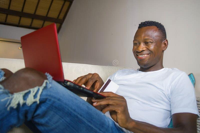 Hombre afroamericano negro feliz y atractivo joven usando tarjeta de crédito y ordenador portátil relajado y alegre en la sala de imagenes de archivo