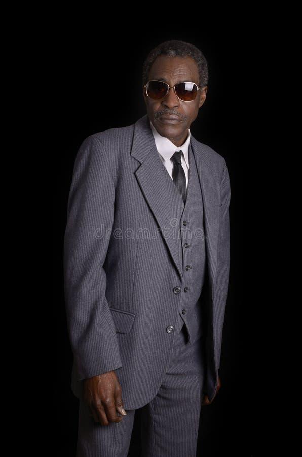 Hombre afroamericano negro mayor en traje gris imagenes de archivo
