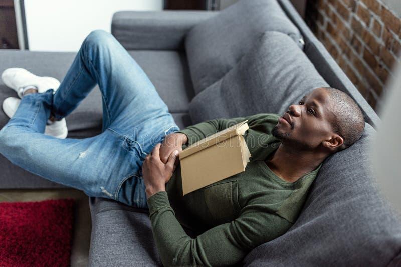 hombre afroamericano pensativo con el libro que parece ausente mientras que se sienta en el sofá imagen de archivo libre de regalías