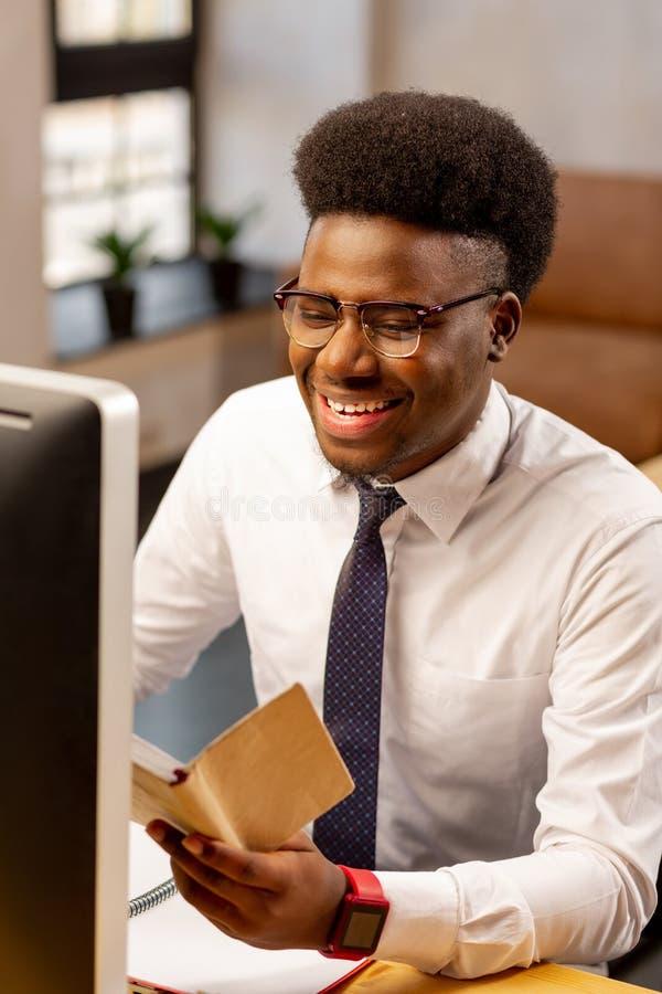 Hombre afroamericano positivo que está en un buen humor fotos de archivo