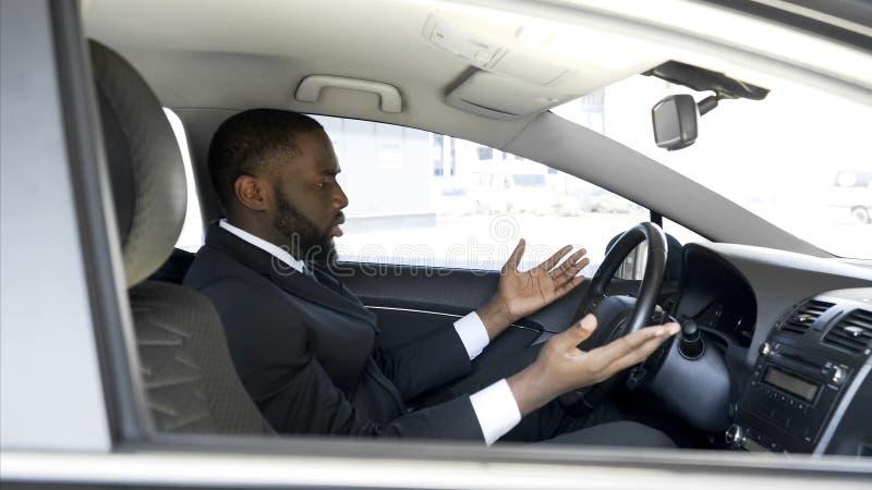 Hombre afroamericano que consigue enojado y nervioso debido a la avería del coche, tensión foto de archivo
