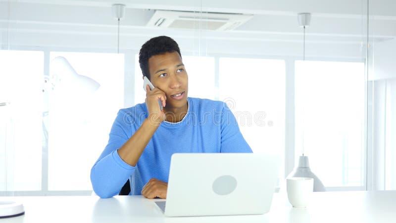 Hombre afroamericano que habla en el teléfono, asistiendo a llamada en el trabajo imágenes de archivo libres de regalías