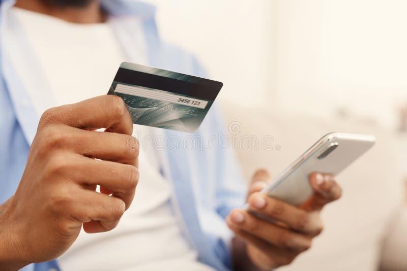 Hombre afroamericano que hace la transacción usando la aplicación móvil foto de archivo libre de regalías