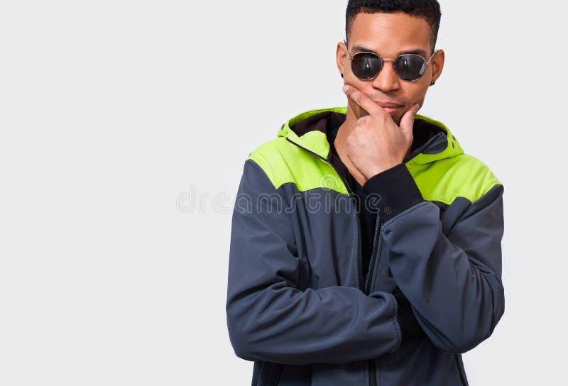 Hombre afroamericano que lleva las gafas de sol redondas del espejo con el finger doblado en la barbilla que frunce el ceño su ca fotografía de archivo libre de regalías