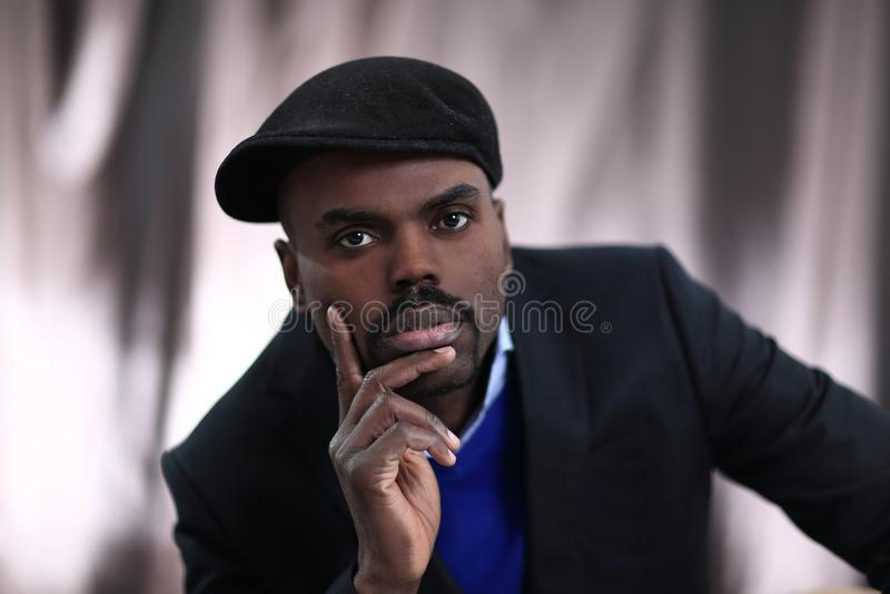 Hombre afroamericano que presenta con la mano en su barbilla imagen de archivo libre de regalías