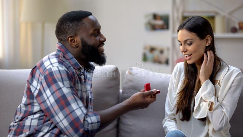 Hombre afroamericano que presenta el anillo de compromiso sorprendido de la señora, proponiendo matrimonio foto de archivo libre de regalías