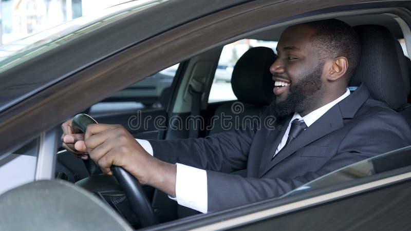 Hombre afroamericano que se sienta en el coche costoso satisfecho y que sonríe, prueba de conducción imagen de archivo libre de regalías