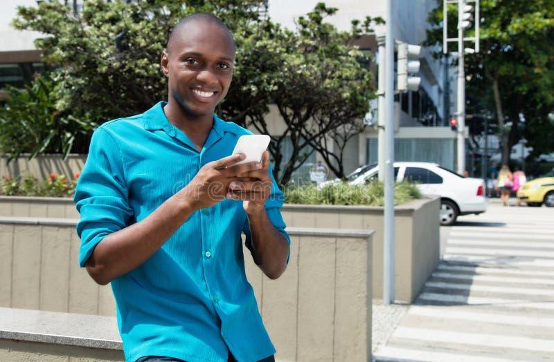 Hombre afroamericano que usa 4g con el teléfono móvil fotografía de archivo libre de regalías