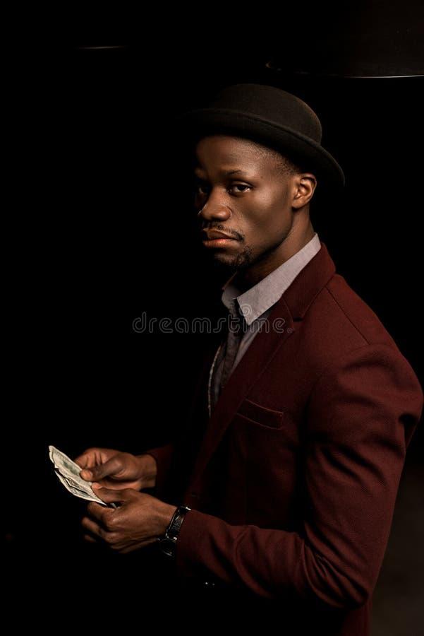 hombre afroamericano rico hermoso en el sombrero que sostiene billetes de banco del dólar, fotografía de archivo