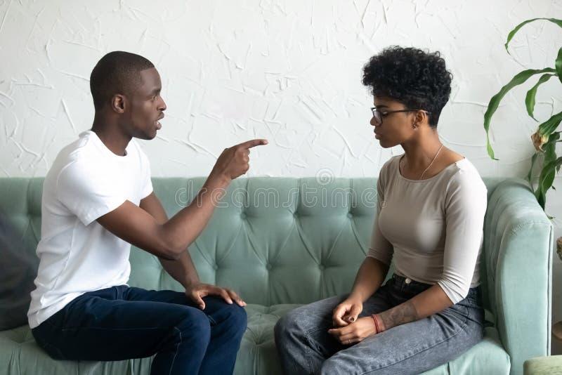 Hombre afroamericano serio que culpa a la mujer trastornada, señalando el finge imagen de archivo