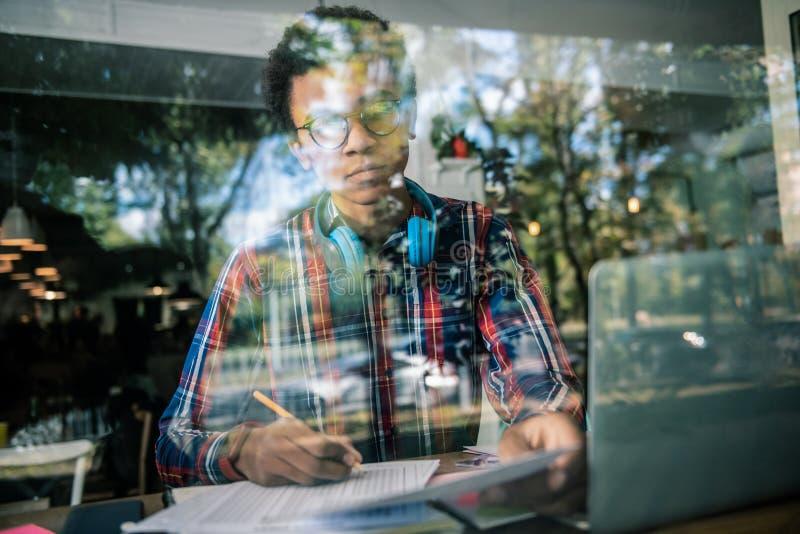 Hombre afroamericano serio que estudia en casa fotos de archivo libres de regalías