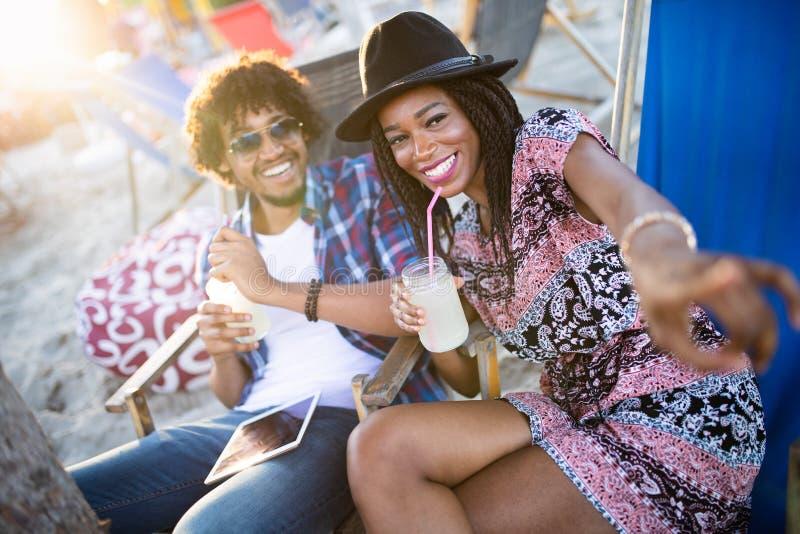 Hombre afroamericano y mujer que ligan hablar en el contador de la barra imagen de archivo