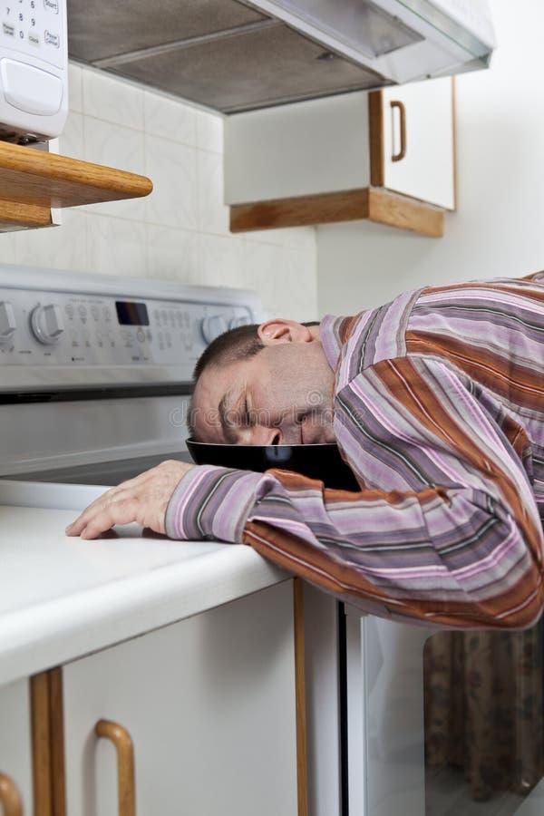 Hombre agotado dormido en un sartén foto de archivo