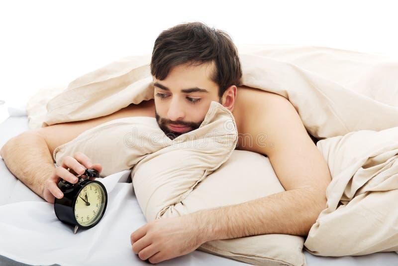 Hombre agotado que es despertado por un despertador imagen de archivo