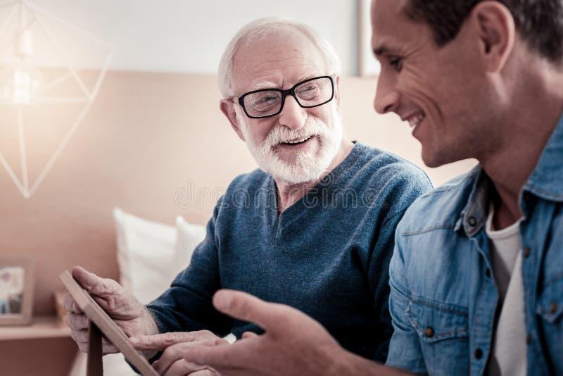 Hombre agradable alegre que habla con su abuelo imagen de archivo libre de regalías