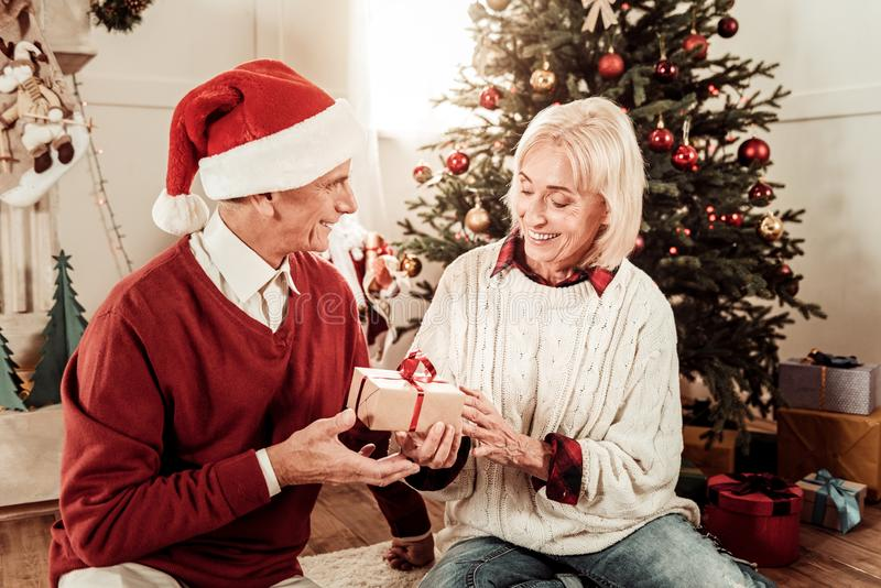 Hombre agradable atento que sienta y que da un presente fotos de archivo libres de regalías