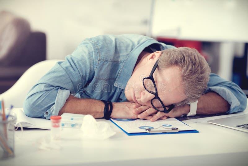 Hombre agradable cansado que duerme en su lugar de trabajo fotos de archivo libres de regalías