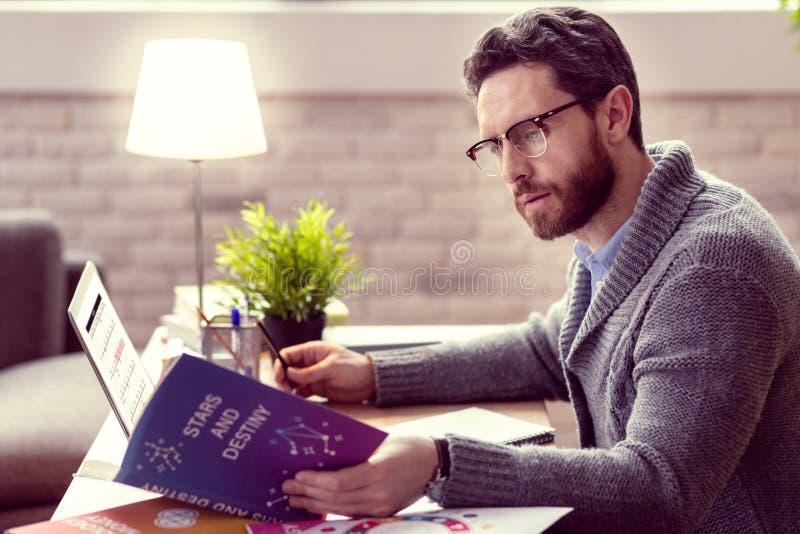 Hombre agradable elegante que lee un libro acerca de la astrología imagenes de archivo