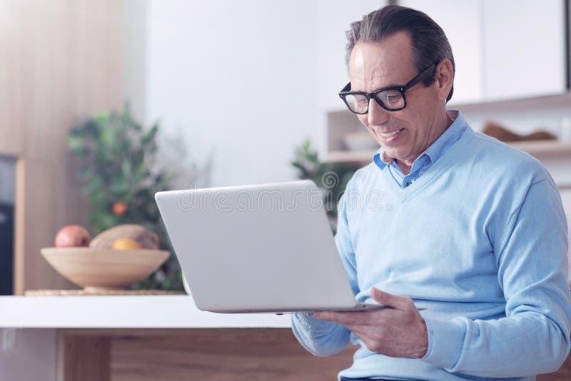 Hombre agradable elegante que trabaja en un ordenador portátil foto de archivo