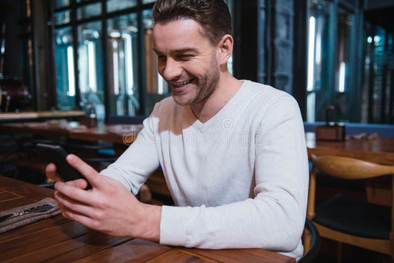 Hombre agradable feliz que mira la pantalla de su smartphone foto de archivo