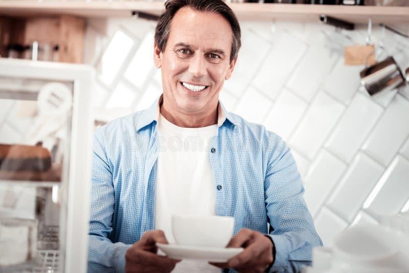 Hombre agradable feliz que ofrece una taza de café fotos de archivo libres de regalías
