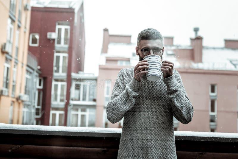 Hombre agradable agradable que goza de su té caliente imagenes de archivo