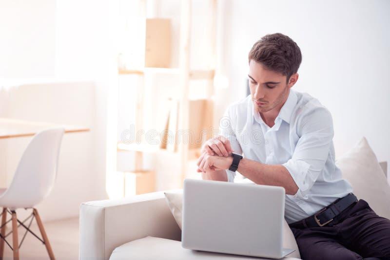 Hombre agradable que mira su reloj elegante foto de archivo