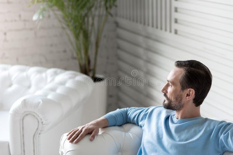 Hombre agradable serio que se relaja en el sofá fotos de archivo