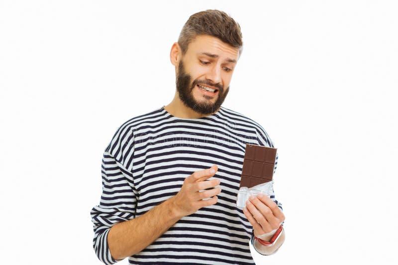 Hombre agradable triste que abre una barra de chocolate fotos de archivo