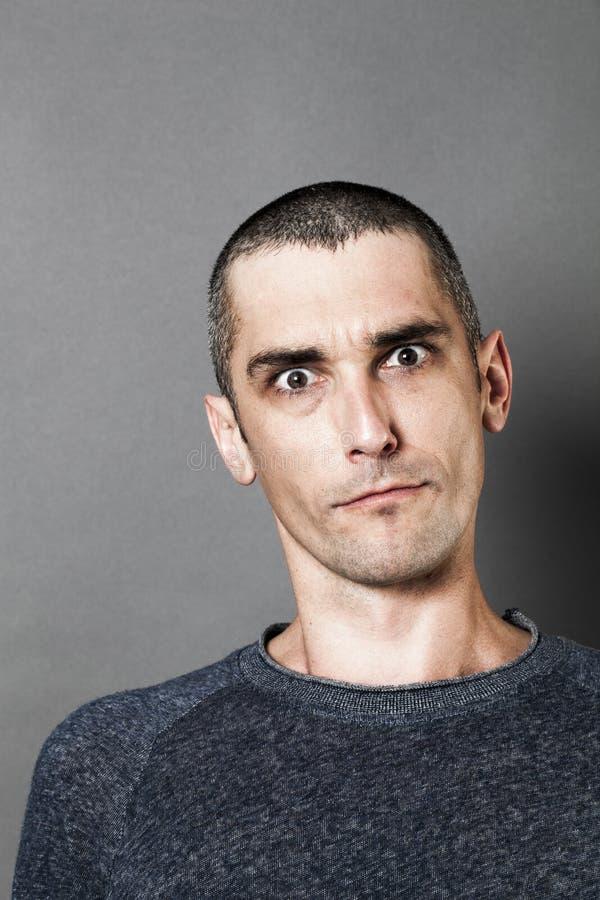 Hombre agresivo que parece escéptico, asustadizo y sorprendido, expresando la sospecha imagen de archivo