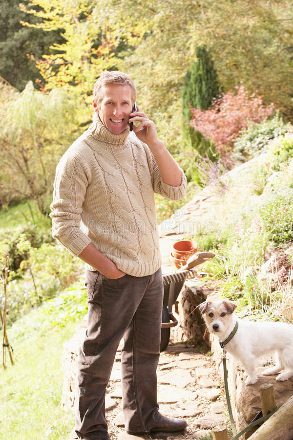 Hombre al aire libre en el teléfono móvil con el perro foto de archivo