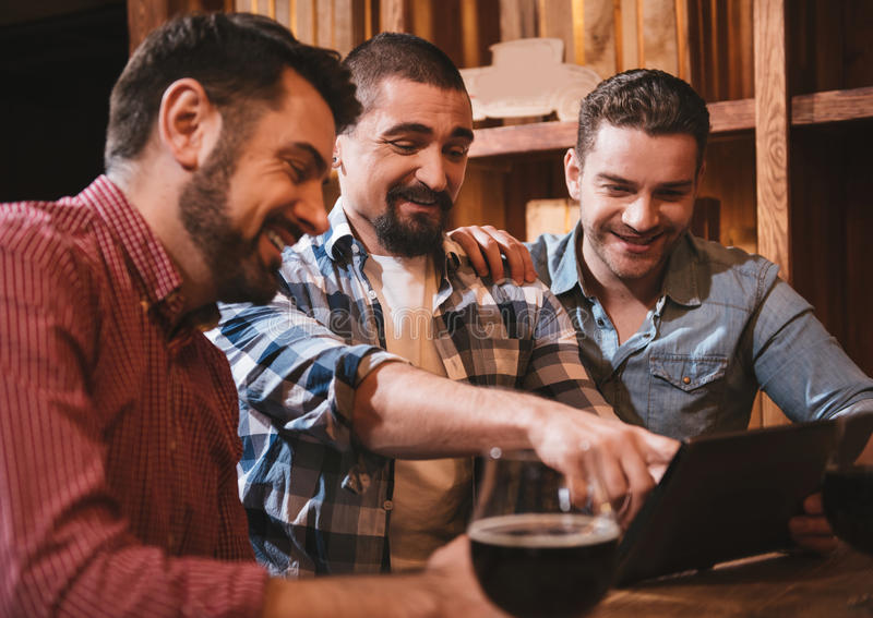 Hombre alegre alegre que señala en la pantalla de la tableta imagen de archivo libre de regalías